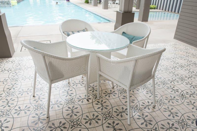 Chaises et avant de tables d'une piscine images libres de droits