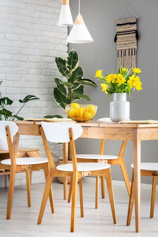 Chaises et lampes blanches dans l'intérieur de salle à manger avec des jonquilles photo libre de droits