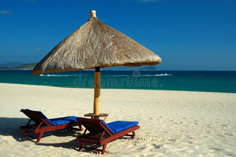 Chaises et parasol de plage par la mer image stock