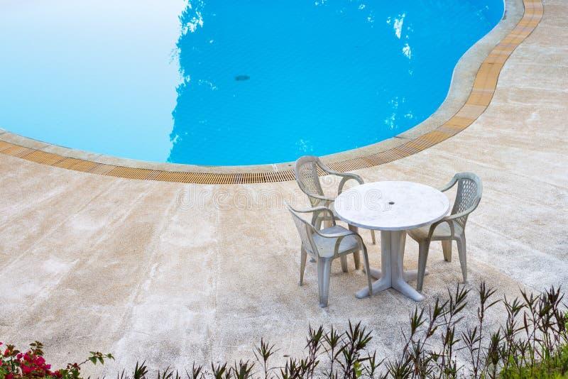 Chaises et table en plastique blanches dans l'espace piscine de natation image stock