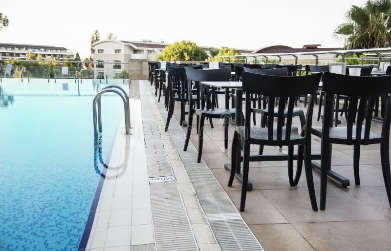 Chaises et tables à côté d'une piscine Concept de luxe de vacances image libre de droits