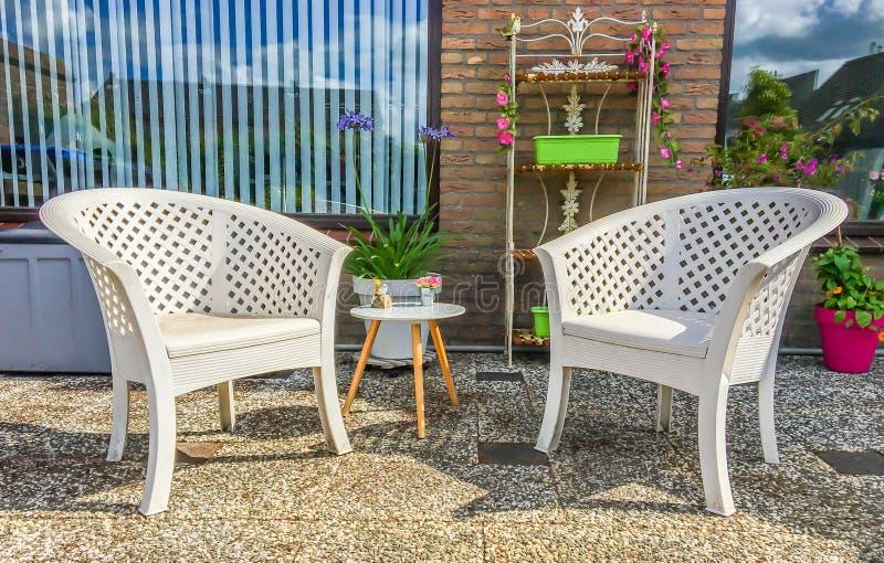 Chaises longues de plastique blanches avec une petite table en bois et décorations de jardin dans l'arrière-cour à la maison photo stock