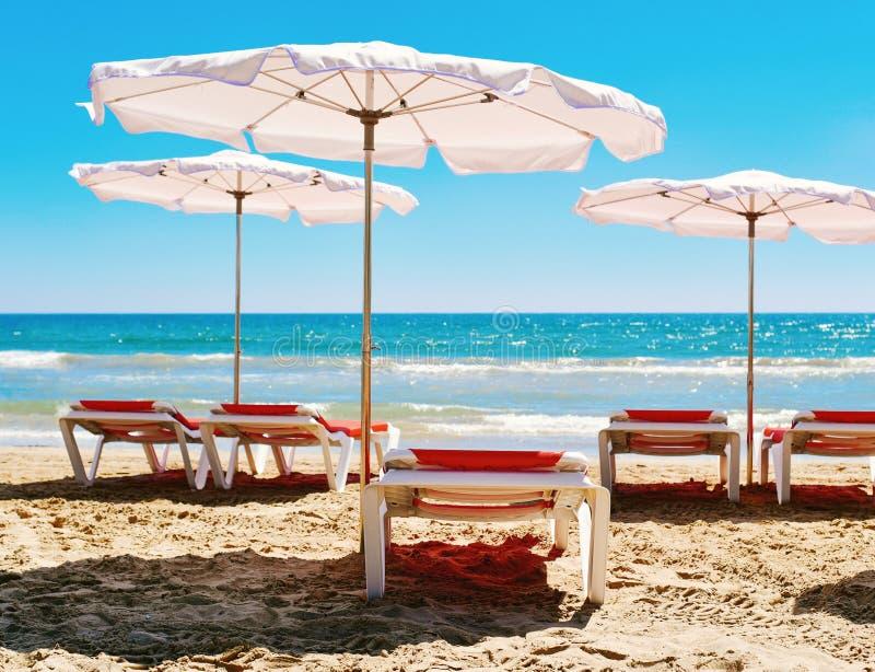 Chaises longues et parapluies dans une plage tranquille photos stock