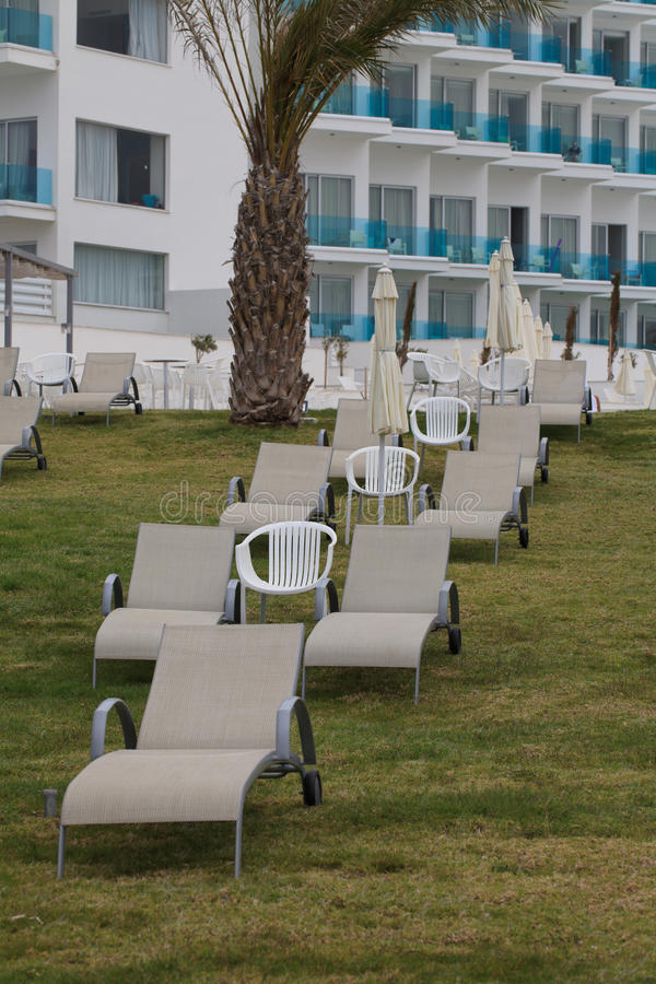Chaises longues sur la pelouse près de la fin d'hôtel  vertical photos stock
