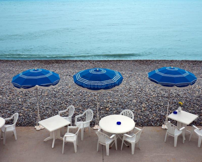 Chaises longues, tables et parasol images stock
