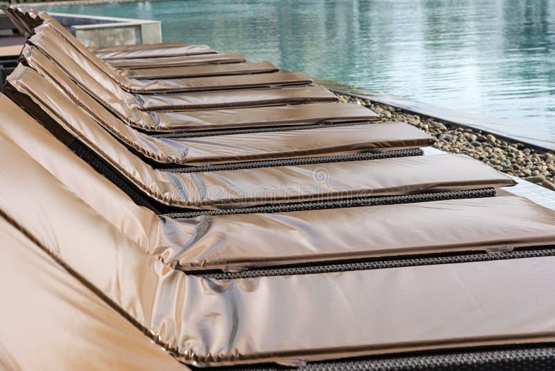Chaises longues vides près de piscine thailand image libre de droits