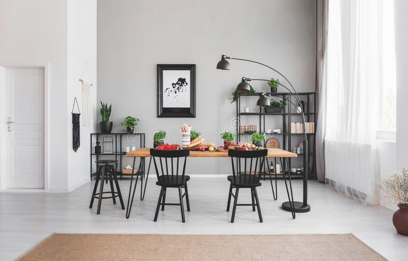 Chaises noires à la table de salle à manger avec la nourriture dans l'intérieur d'appartement avec la lampe et l'affiche sur le m photos stock