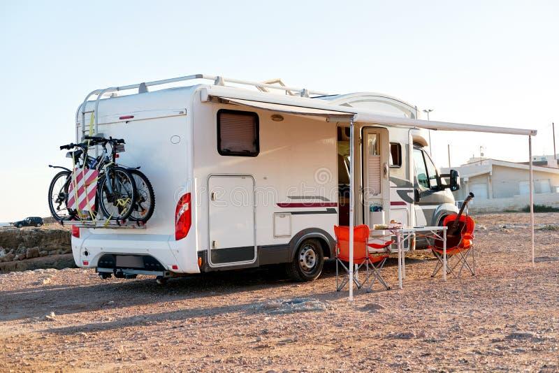 Chaises pliantes et table vides sous l'auvent près de la remorque de campeur de camping-car photographie stock libre de droits