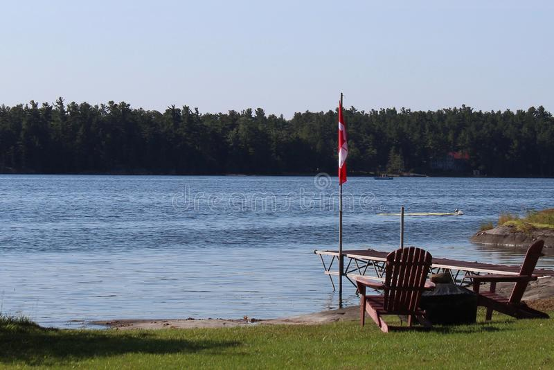 Chaises regardant au-dessus de la belle vue de lac avec le drapeau de Canada image libre de droits