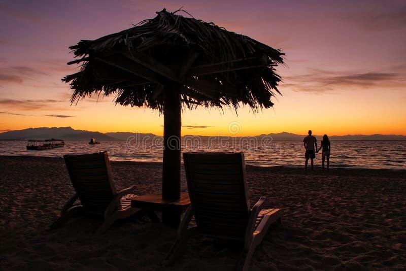 Chaises silhouettées du soleil avec le parapluie couvert de chaume sur une plage au sunr photos stock