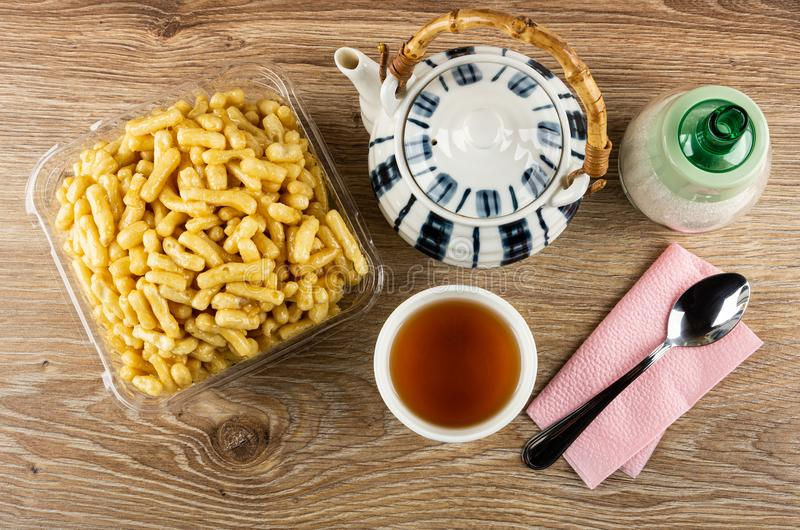 Chak-Chak in transparent box, teapot, sugar bowl, cup of tea, spoon on napkin on wooden table. Top view stock photos