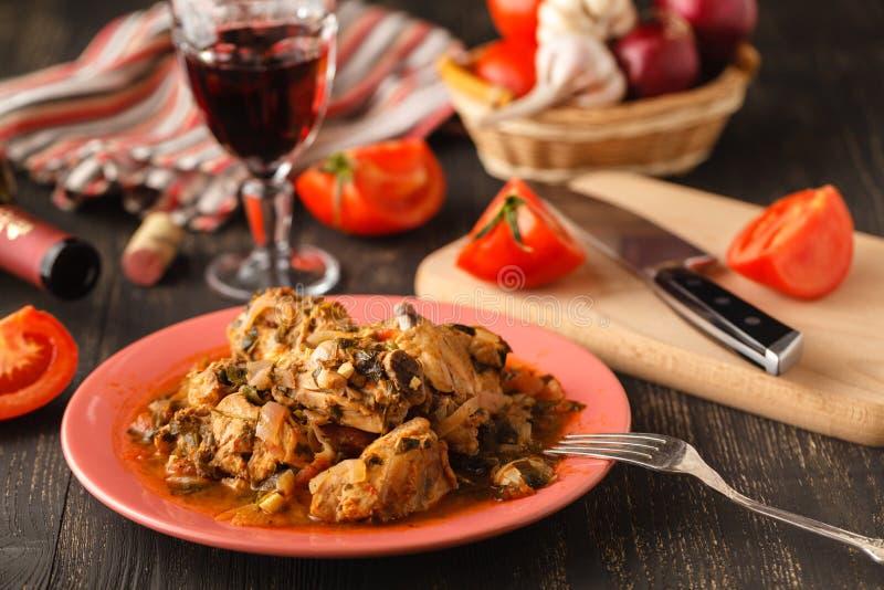 Chakhokhbili - chiken Eintopfgericht mit Korianderpetersilie in der Tomatensauce in einer Lehmschüssel, traditioneller Teller der stockfotos