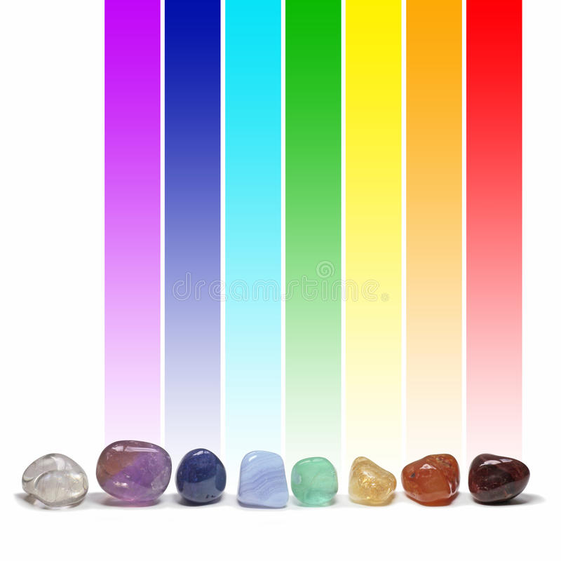 Chakra healing crystals and their colors. A single row of eight tumbled healing crystals each with their corresponding chakra color above in a long graduated stock illustration