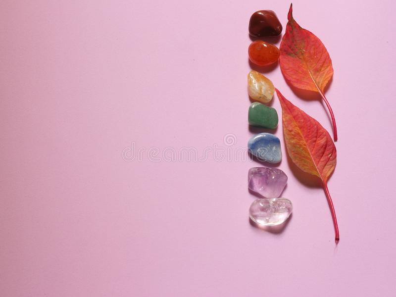Chakra healing stones on pink millennial background royalty free stock images