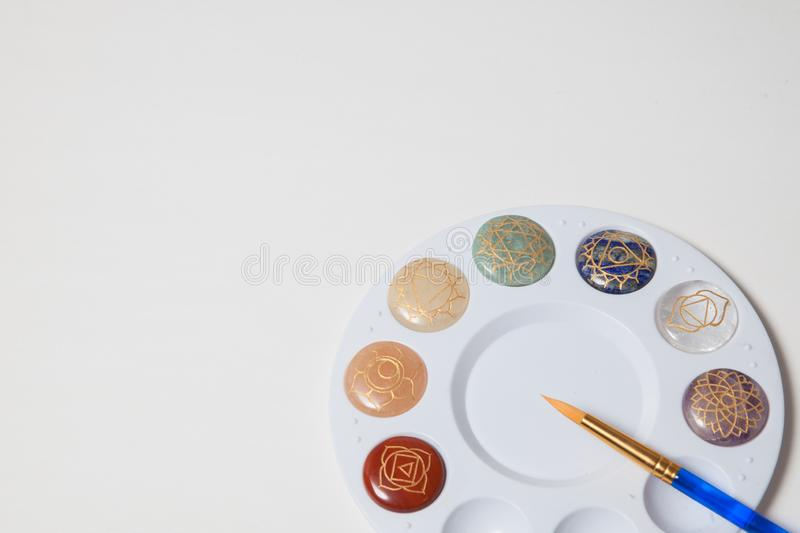 Chakra stones and a paint brush. On a white background royalty free stock image