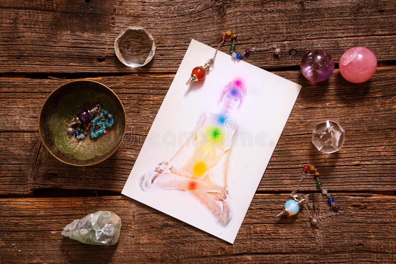 Chakras over a human body. Chakras illustrated over human body with natural crystals and pendulum royalty free stock images