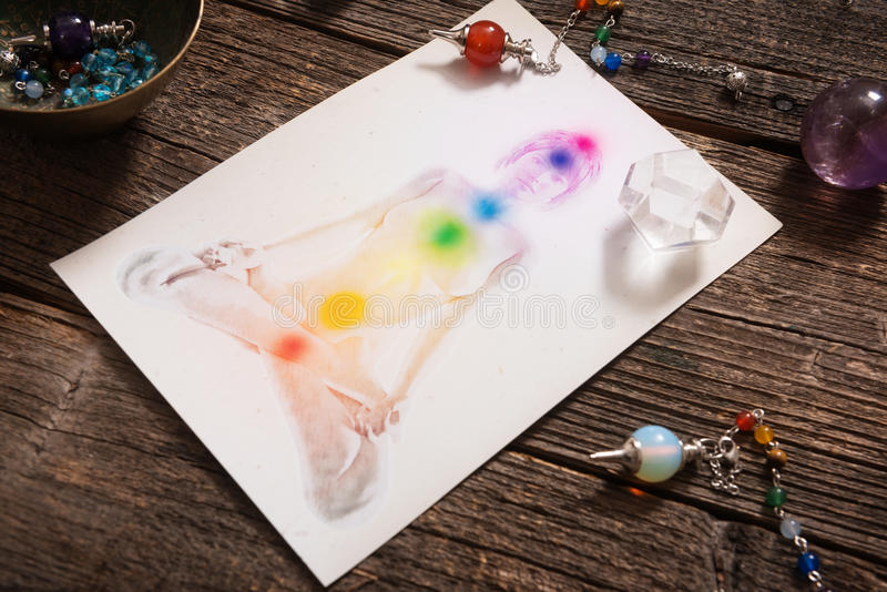 Chakras over a human body. Chakras illustrated over human body with natural crystals and pendulum royalty free stock photos