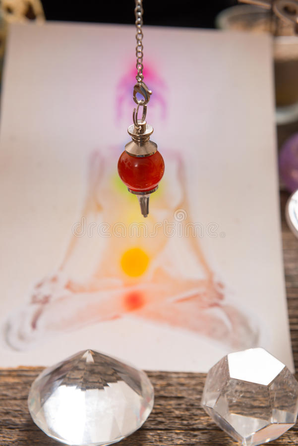 Chakras over a human body. Chakras illustrated over human body with natural crystals and pendulum stock photography