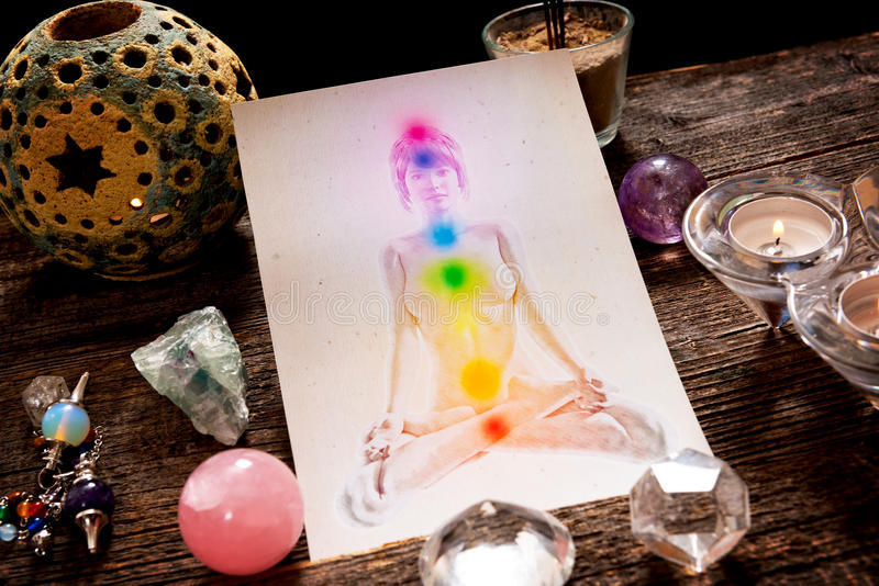 Chakras over a human body. Chakras illustrated over human body with natural crystals and pendulum stock image