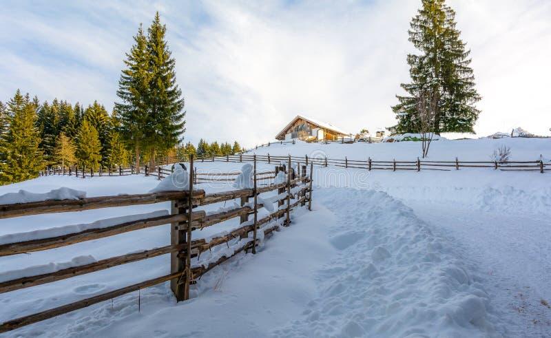Chalé do inverno na montanha Fugas e trajeto dos caminhantes na neve imagens de stock royalty free