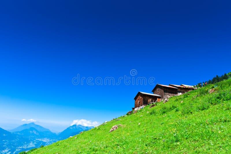 Chalés alpinos na inclinação de montanha verde imagem de stock