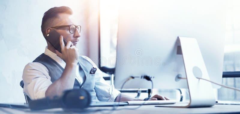 Chaleco barbudo de Wearing White Shirt del hombre de negocios del primer que trabaja la mesa moderna del inicio del desván Uso cr fotos de archivo