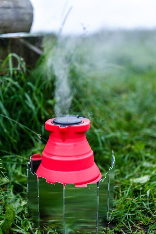 Chaleira de acampamento de Fodable com a água a ferver que está em fogão ardente fotos de stock royalty free