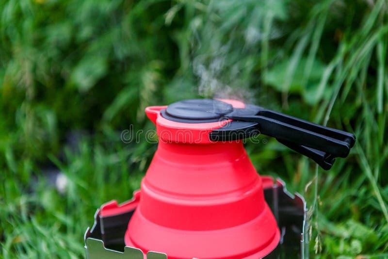 Chaleira de acampamento de Fodable com a água a ferver que está em fogão ardente foto de stock