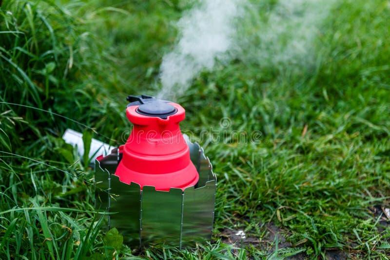 Chaleira de acampamento de Fodable com a água a ferver que está em fogão ardente foto de stock royalty free