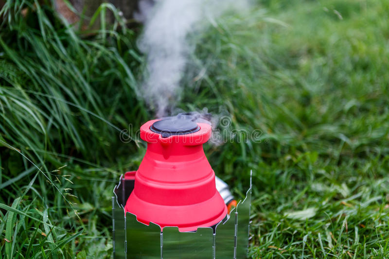 Chaleira de acampamento de Fodable com a água a ferver que está em fogão ardente imagem de stock royalty free