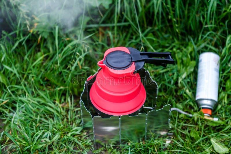 Chaleira de acampamento de Fodable com a água a ferver que está em fogão ardente imagens de stock royalty free