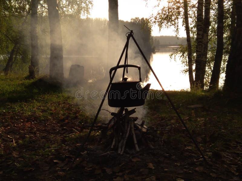 Chaleira de acampamento do turista nas fervuras do fogo no fundo da floresta e do rio imagens de stock royalty free