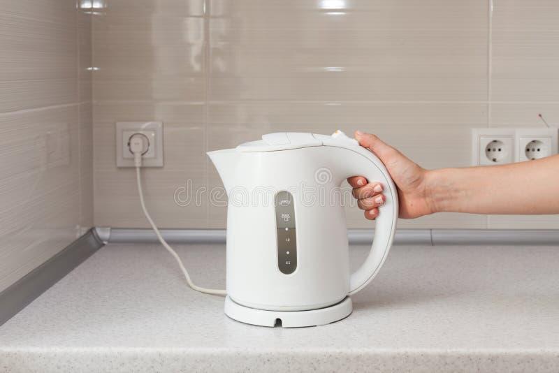 Chaleira elétrica à disposição no fundo da cozinha imagem de stock