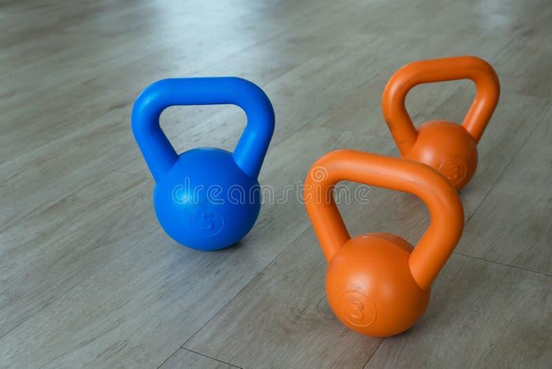 Chaleira-sino alaranjado azul para o exercício e o esporte do levantamento de peso no fundo de madeira do assoalho do gym fotografia de stock