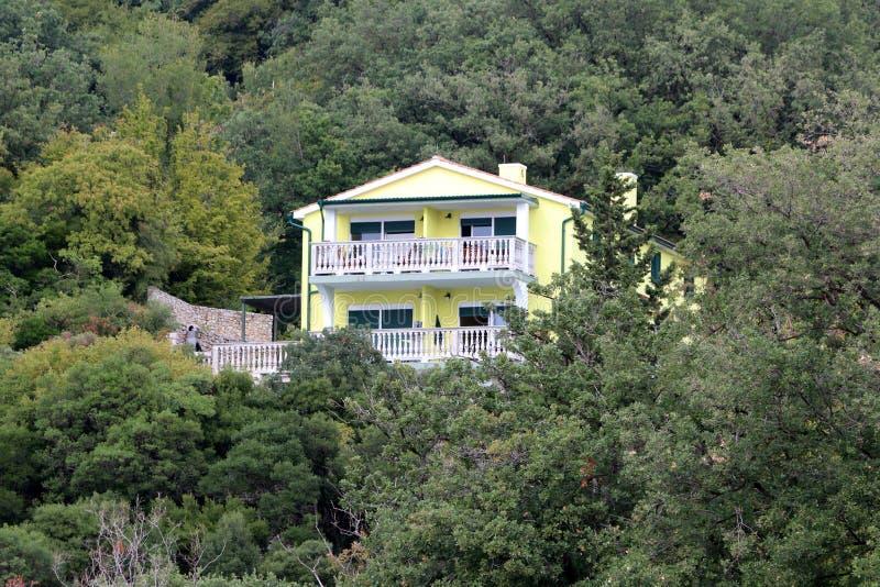 Chalet amarillo mediterráneo moderno con la cerca de piedra blanca del balcón y la pared de piedra tradicional en el patio traser fotos de archivo