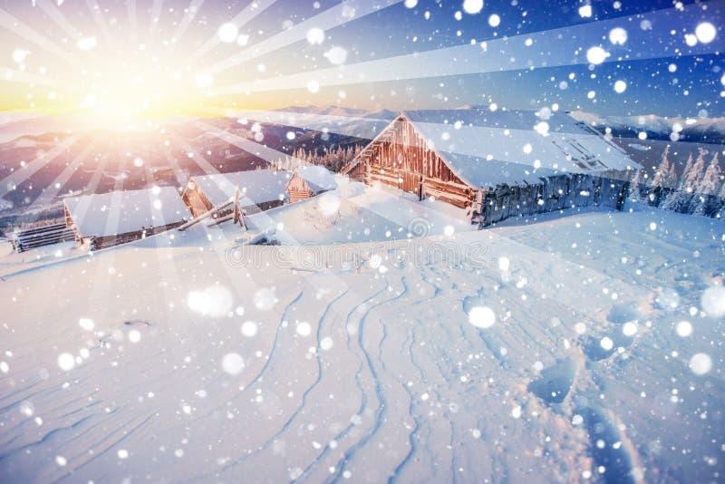 Chalet i bergen på solnedgången Vinterhälsningar arkivbild