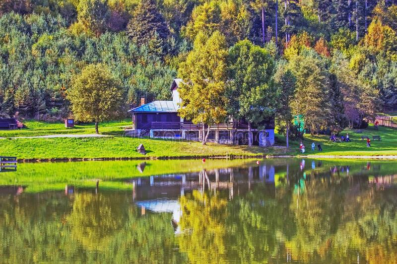 Chalet by lake in Autumn royalty free stock image