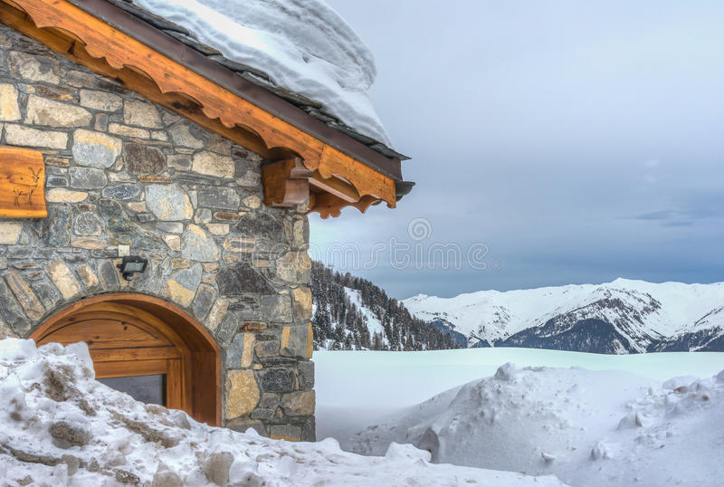 Chalet in the snow on mountain background. The Alps at Aime la Plagne in France royalty free stock photography