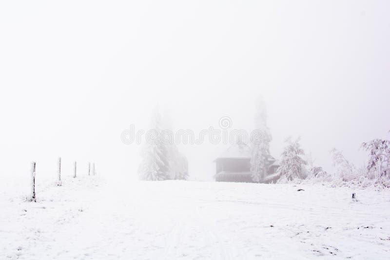 Chalet som omges av snöig och djupfrysta slättar royaltyfri foto