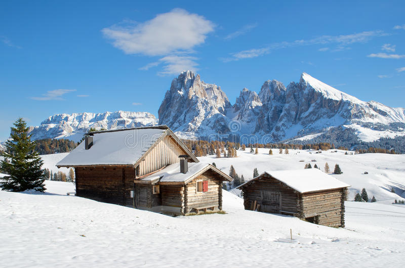 Chalets on the Alpe di Siusi. Wooden mountain chalets with a view on the Langkofel and Plattkofel (Sassolungo and Sassopiatto) dolomites mountains at the Alpe di royalty free stock image