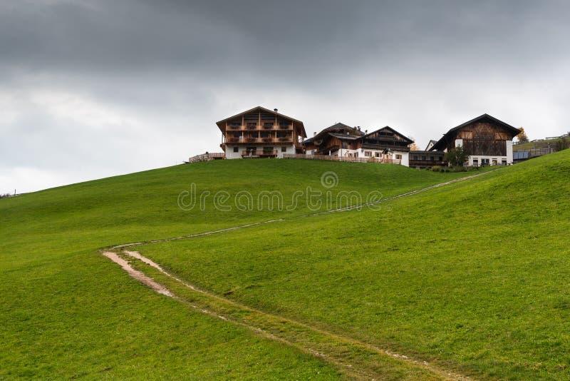 Chalets de madera en el acantilado cubierto de campos verdes en los Alpes italianos imágenes de archivo libres de regalías