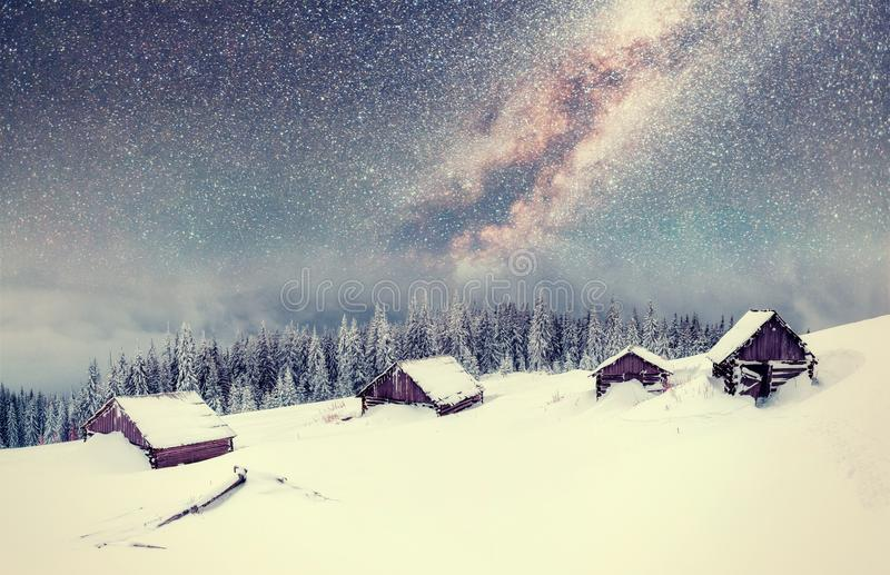 Chalets in the mountains at night under the stars. Magic event in frosty day. In anticipation of the holiday. Dramatic scenes. Carpathians, Ukraine, Europe royalty free stock images