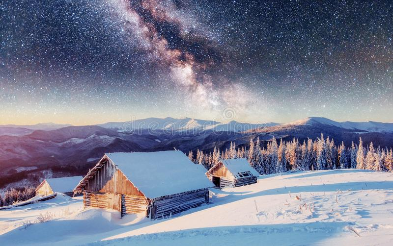 Chalets in the mountains at night under the stars. Magic event in frosty day. In anticipation of the holiday. Dramatic scenes. Carpathians, Ukraine, Europe stock image