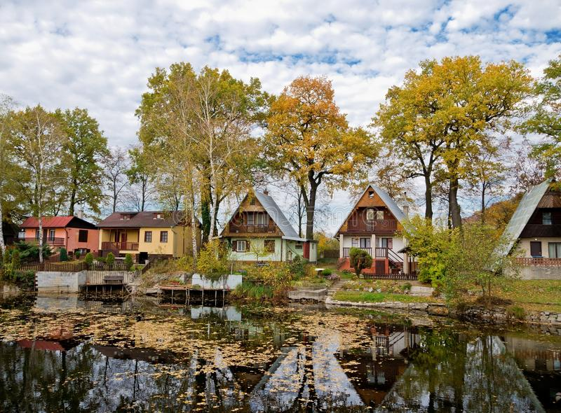 Chalets and a pond. Few chalets on a bank of a lake in autumn stock photos