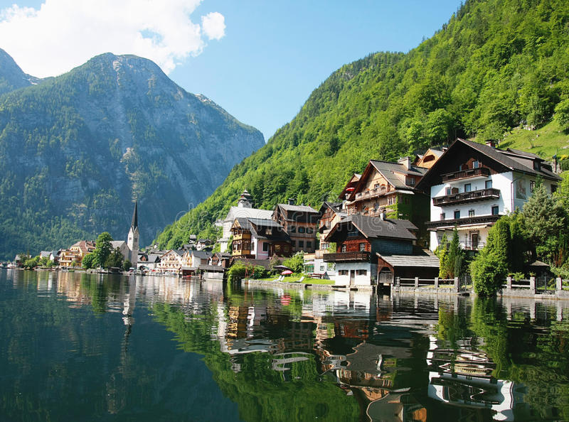 Chalets reflecting on lake. Scenic view of chalets reflecting on lake with forested mountains in background royalty free stock photography