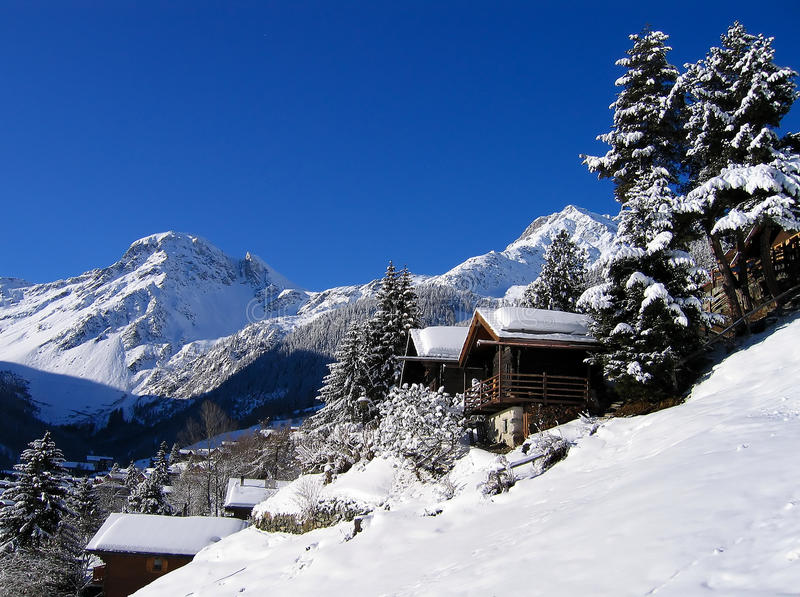 Chalets in a snow white valley. In a ski area in the Swiss Alps with a clear sky royalty free stock image