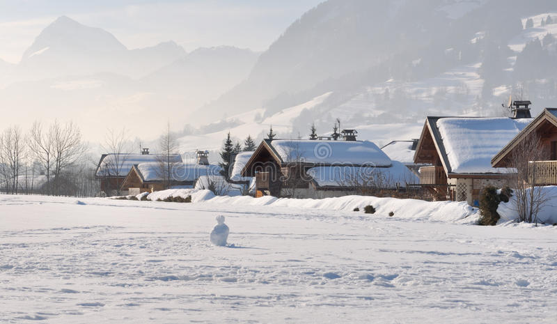 Chalets under snow. Wooden chalets in a village in the mountains covered with snow royalty free stock image
