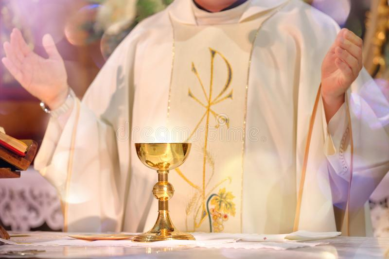 Chalice at the altar with rays of light and Priest celebrate mass stock image