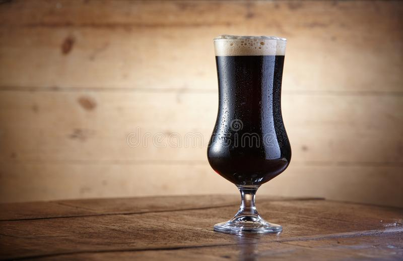 Chalice of dark beer standing on wooden table royalty free stock image