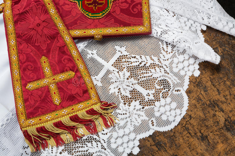 Chalice veil and maniple. 19th century red damask chalice veil and maniple on a white lace catholic priest surplice royalty free stock photos